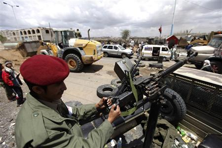 A soldier riding at the back of a pick-up truck mans a weapon as soldiers secure a street, where barricades are being dismantled in Sanaa April 10, 2012. REUTERS/Mohamed al-Sayaghi