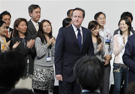 Britain's Prime Minister David Cameron (C) is welcomed by Nissan Motors employees upon his arrival at the company's global headquarters in Yokohama, south of Tokyo April 10, 2012. REUTERS/Issei Kato
