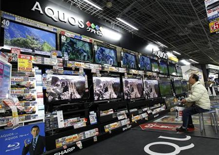 A man watches Sharp's television sets at an electronic shop in Tokyo March 19, 2012. REUTERS/Kim Kyung-Hoon