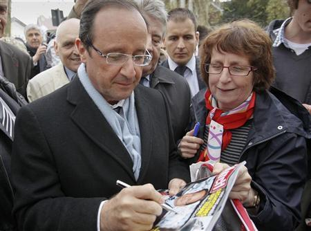 Francois Hollande (L), Socialist Party candidate for the 2012 French presidential election, signs autographs during a campaign visit in Besancon, eastern France, April 10, 2012. REUTERS/Robert Pratta
