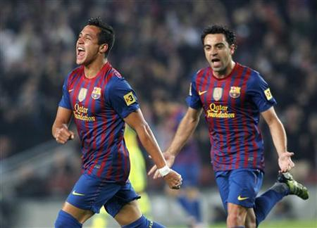 Barcelona's Alexis Sanchez (L) and Xavi Hernandez celebrate a goal against Getafe during their Spanish First division soccer match at Camp Nou stadium in Barcelona, April 10, 2012. REUTERS/Albert Gea