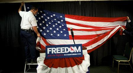 Workers hang a U.S. flag as the backdrop for conservative Rick Santorum's stage before his announcement that he is dropping out of the Republican presidential race in Gettysburg, Pennsylvania April 10, 2012. REUTERS/Mark Makela