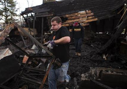 Frank Sisler struggles to carry a burned cart out of a destroyed garage following a large wildfire in Manorville, New York April 10, 2012. REUTERS/Lucas Jackson