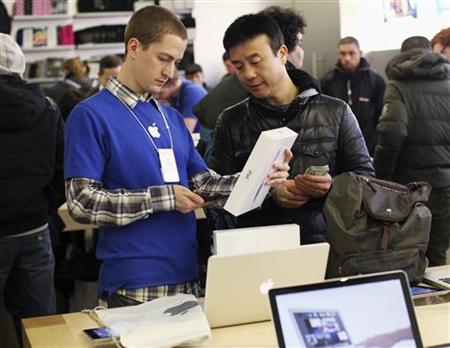 An Apple Store employee sells Apple's new iPad to a customer at the 5th Avenue Apple Store in New York, March 16, 2012. REUTERS/Shannon Stapleton