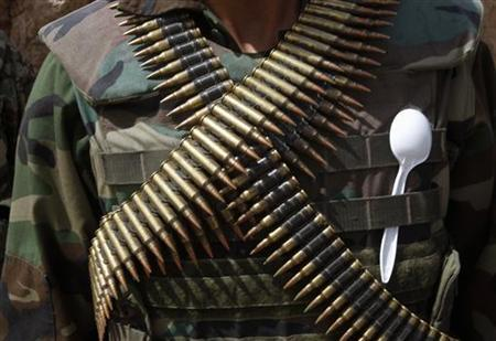 An Afghan soldier carries a plastic spoon on his vest as he slings a belt of bullets around his neck, in the Maiwand district of Kandahar province, southern Afghanistan April 9, 2012. REUTERS/Baz Ratner