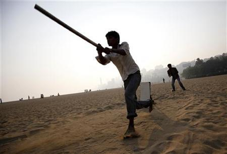 A man hits a ball with an improvised stick for a bat as people play cricket by the beach in Mumbai February 2, 2011. REUTERS/Danish Siddiqui/Files