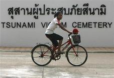 Сельский житель проезжает на велосипеде мимо кладбища жертв цунами в Панг-Нга, Таиланд 25 декабря 2007. Таиланд, Индия, Шри-Ланка выпустили предупреждения об угрозе цунами после мощного землетрясения магнитудой 8,7 балла по шкале Рихтера в среду в Индонезии. REUTERS/Chaiwat Subprasom