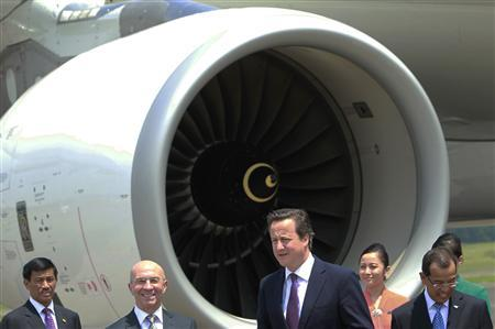 Britain's Prime Minister David Cameron (C) stands near Garuda Indonesia Airbus A330-200 at Halim Perdana Kusuma airport in Jakarta April 11, 2012.   REUTERS/Beawiharta