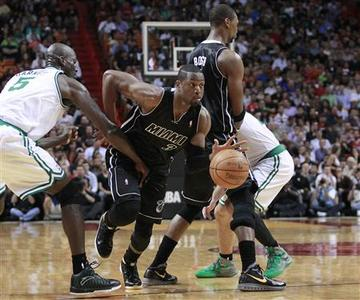 Miami Heat's Dwyane Wade (C) moves past Boston Celtics' Kevin Garnett (L) during the first half of their NBA basketball game in Miami, Florida April 10, 2012. REUTERS/Andrew Innerarity