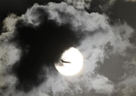 A passenger aircraft is silhouetted against the rising sun after taking off from New Delhi's Indira Gandhi International Airport April 3, 2012. REUTERS/B Mathur