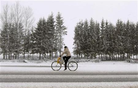 A woman rides a bicycle during heavy snow fall near the village of Novye Chemodany, some 200 km (125 miles) east of Minsk, April 9, 2012. REUTERS/Vasily Fedosenko
