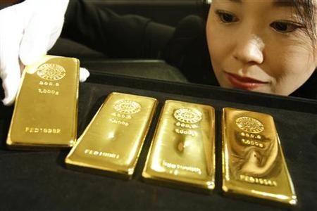 An employee poses with gold bars at the Ginza Tanaka store in Tokyo October 23, 2009. REUTERS/Issei Kato
