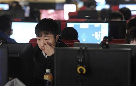 A man scratches his face as he uses a computer at an internet cafe in Hefei, Anhui province March 16, 2012. REUTERS/Stringer