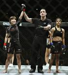 Referee declares Singapore's Nicole Chua (L) as winner as after she defeated India's Jeet Toshi in their One Fighting Championship (FC) mixed martial arts (MMA) fight at the Singapore Indoor Stadium in this March 31, 2012, file photo. REUTERS/Tim Chong/Files