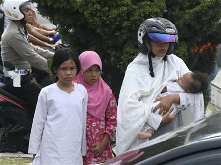 A woman carries her baby to a safe place in Banda Aceh after a strong earthquake struck Indonesia province April 11, 2012. REUTERS/Junaidi Hanafiah