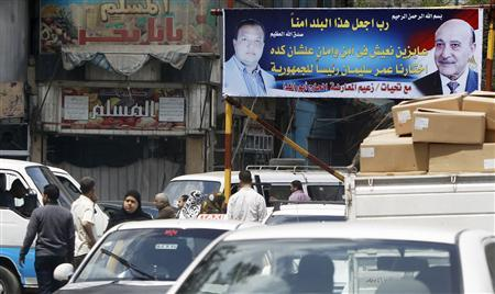 People walk past under a banner by El Hag Abo Randa (L in banner), created for presidential candidate and Egypt's former vice president Omar Suleiman (R in banner), in Cairo April 11, 2012. REUTERS/Amr Abdallah Dalsh