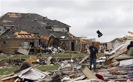 John Shipman tosses a boot from the remains of his mother's home during the cleanup effort in Forney, Texas, April 4, 2012. REUTERS/Tim Sharp