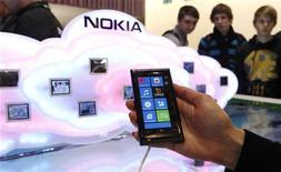 Membro da Nokia posa com celular da empresa para apresentar software de computação em nuvem em Hanover. A Nokia alertou que seu segmento de celulares deve registrar perdas nos dois primeiros trimestres deste ano, enquanto se esforça para renovar sua linha de produtos e competir com Apple e Samsung, fazedo com que suas ações desabassem 19 por cento. Foto de arquivo. 06/03/2012    REUTERS/Fabrizio Bensch