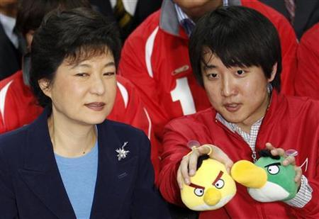 The ruling Saenuri Party's interim leader Park Geun-hye (L) and a party member watch a television report on an exit poll of the parliament elections at the party's headquarters in Seoul April 11, 2012. REUTERS/Kim Kyung-Hoon