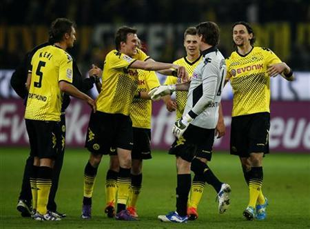 Players of Borussia Dortmund celebrate with goalkeeper Roman Weidenfeller after defeating Bayern Munich during their German first division Bundesliga soccer match in Dortmund, April 11, 2012. Dortmund won the match 1-0. REUTERS/Kai Pfaffenbach