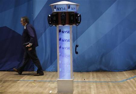 A trader walks past a phone hanging off the hook on the floor of the New York Stock Exchange September 27, 2011. REUTERS/Brendan McDermid