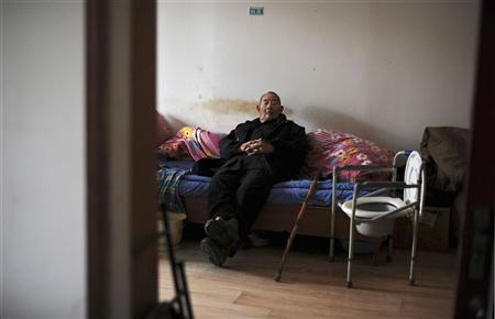 An elderly man sits in his bed at a nursing home in Hefei, Anhui province March 20, 2012. REUTERS/Stringer