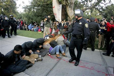 A University of California Davis police officer pepper-sprays students during their sit-in at an ''Occupy UCD'' demonstration in Davis, California in this November 18, 2011 file photo. University of California officials and campus police exercised poor judgment and excessive force in the pepper-spraying of students aligned with the Occupy Wall Street movement last fall, an independent review of the incident found on April 11, 2012. REUTERS/Brian Nguyen/Files