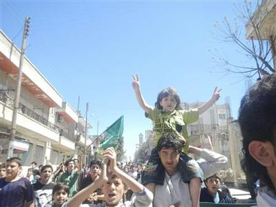 Demonstrators protest against Syria's President Bashar Al-Assad in Kafranbel, near Idlib April 10, 2012. REUTERS/Raad Al Fares/Shaam News Network/Handout (SYRIA - Tags: POLITICS CIVIL UNREST) FOR EDITORIAL USE ONLY. NOT FOR SALE FOR MARKETING OR ADVERTISING CAMPAIGNS. THIS IMAGE HAS BEEN SUPPLIED BY A THIRD PARTY. IT IS DISTRIBUTED, EXACTLY AS RECEIVED BY REUTERS, AS A SERVICE TO CLIENTS