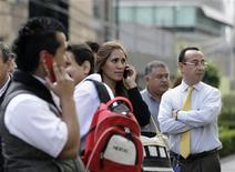 People talk on their mobile phones after being evacuated from their buildings following an earthquake in Mexico City April 11, 2012. A strong earthquake hit Mexico on Wednesday, shaking buildings in the capital and sending people rushing out of offices onto the streets, though there were no early reports of major damage.The U.S. Geological Survey said the 7.0 magnitude quake struck in the western state of Michoacan at a depth of 40.8 miles (65.6 km). REUTERS/Henry Romero