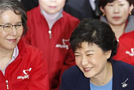 Park Geun-hye (R), interim leader of the ruling Saenuri Party, and party members smile as they watch a television report on an exit poll of the parliament elections at the party's headquarters in Seoul April 11, 2012. REUTERS/Kim Kyung-Hoon