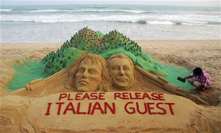Indian sand artist Sudarshan Patnaik gives the finishing touches to a sand art sculpture created by him appealing for the release of two Italian tourists, on a beach in Puri, Orissa, March 20, 2012. REUTERS/Stringer/Files