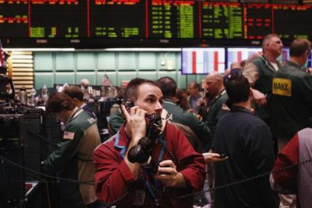 A trader works with three telephone receivers in the crude oil and natural gas options pit on the floor of the New York Mercantile Exchange March 7, 2011. REUTERS/Lucas Jackson