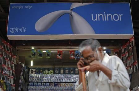 A man walks past a road side shop selling mobile phones and accessories displaying Uninor advertisement in Mumbai February 2, 2012. REUTERS/Danish Siddiqui
