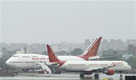 Air India aircrafts stand on the tarmac during heavy rains at the Indira Gandhi International Airport in New Delhi July 15, 2010. REUTERS/B Mathur/Files