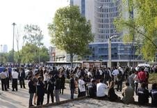 People gather on Paseo de la Reforma avenue, after being evacuated from their buildings following an earthquake in Mexico City April 11, 2012. REUTERS/Alejandro Dias