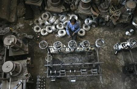 An employee thins the gauge of iron wire which is used to make iron net inside a manufacturing unit on the outskirts of Jammu April 12, 2012. REUTERS/Mukesh Gupta