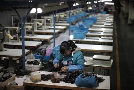 A labourer works at an empty shoe factory in the city of Wenzhou, in Zhejiang province, in this February 18, 2011 file photo. REUTERS/Carlos Barria/Files