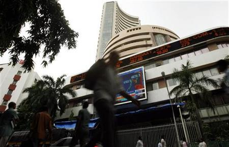 People walk pass the Bombay Stock Exchange (BSE) building displaying India's benchmark share index on its facade, in Mumbai July 31, 2009. REUTERS/Punit Paranjpe/Files