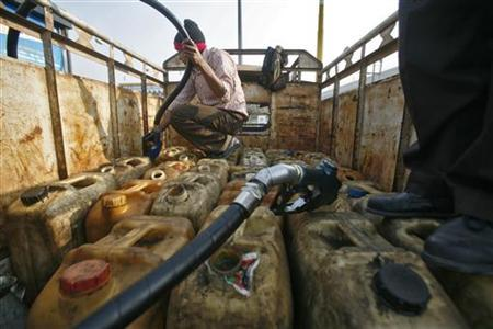 Workers fill diesel in plastic containers at a fuel station in Noida in Uttar Pradesh January 27, 2011. REUTERS/Parivartan Sharma/Files
