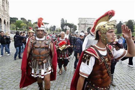 Men dressed as ancient Roman centurions walk during a protest in front of the Colosseum in Rome April 12, 2012. REUTERS/Tony Gentile