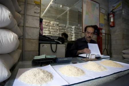 Samples of rice are seen on the desk as a rice wholesaler checks his books while waiting for customers at his shop in south Tehran June 18, 2008. REUTERS/Caren Firouz