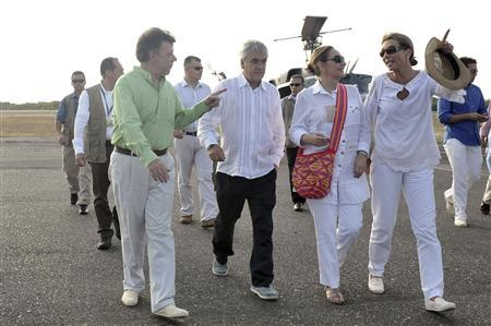 Presidents of Colombia, Juan Manuel Santos (front L) and Chile, Sebastian Pinera (front 2nd L) walk with their respective wives Maria Clemencia Rodriguez (R) and Cecilia Morel to a plane for a visit to an indigenous reservation in the Sierra Nevada de Santa Marta, in Cartagena April 12, 2012. REUTERS/Andres Piscov-SIG/Handout
