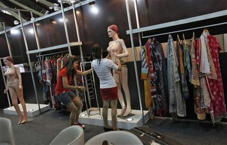 Exhibitors from Pakistan prepare a mannequin on display during the preparations for the Lifestyle Pakistan Exhibition in New Delhi April 12, 2012. REUTERS/Adnan Abidi