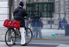 Un passante in bici davanti a uno schermo con le quotazioni di borsa a Milano. REUTERS/Alessandro Garofalo  (ITALY - Tags: POLITICS SOCIETY)