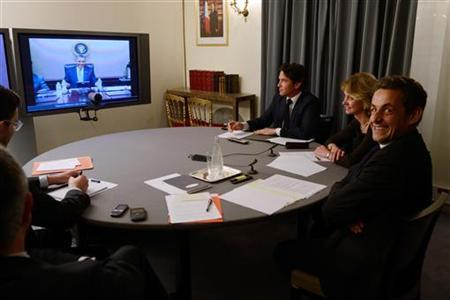 France's President Nicolas Sarkozy (R) and Elysee's diplomatic adviser for US Damien Loras (3rdR) take part in a video conference with U.S. President Barack Obama (on screen) at the Elysee palace in Paris April 12, 2012. REUTERS/Eric Feferberg/Pool