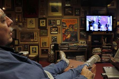 Dennis Turpin smokes a cigar as he watches the U.S. Republican presidential debate at Castro's Back Room in Manchester, New Hampshire January 7, 2012. REUTERS/Jessica Rinaldi