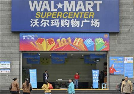 Employees stand in front of the gate to a Wal-Mart Supercenter in Chongqing municipality October 24, 2011. REUTERS/Stringer