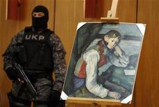 "A Serbian special police guards what is believed to be an impressionist masterpiece ""Boy in a Red Waistcoat"" by Paul Cezanne in Belgrade April 12, 2012. Police in Serbia believe they have recovered an Impressionist masterpiece by Paul Cezanne worth at least $109 million that was stolen at gunpoint in one of the world's biggest art heists four years ago, a police official said on Thursday. The canvas - Boy in a Red Waistcoat - was one of four paintings stolen from a Swiss art gallery in 2008 by a trio of masked robbers who burst in just before closing time and told staff to lay on the floor while they took what they wanted. REUTERS/Marko Djurica"