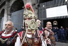 Men dressed as ancient gladiators stand during a protest in front of the entrance of Colosseum in Rome April 12, 2012. REUTERS/Tony Gentile