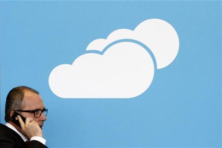 A visitor uses his mobile phone as he walks past the Microsoft booth with a logo for cloud computing software application at the CeBit computer fair in Hanover, March, 6, 2012. REUTERS/Fabrizio Bensch